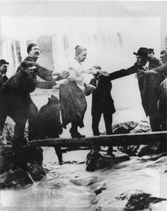 A dazed and dishevelled Annie Taylor is helped to shore after her harrowing journey over the falls in a barrel.