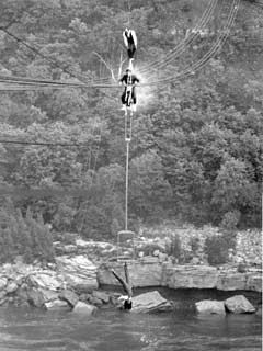 Henri Rechatin balances atop a motorcycle being driven by his friend Frank Lucas while Rechatin's wife dangles above the rapids by a rope